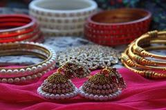 Indische Haardekoration sowie viele Armbänder und Bälle liegen auf einem farbigen traditionellen Schal stockbilder