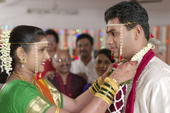 Indische hindische Braut, die Bräutigam betrachtet und Girlande in der Maharashtrahochzeit austauscht stockfoto