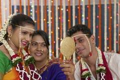 Indische hindische Braut mit ihrer Schwiegermutter und Bräutigam, die im Spiegel in der Maharashtrahochzeit schauen Stockfotos