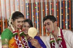 Indische hindische Braut mit ihrer Schwiegermutter und Bräutigam, die im Spiegel in der Maharashtrahochzeit schauen Stockbild