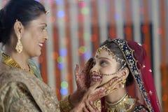 Indische Hindoese Bruid die klaar met hulp van moeder worden. Stock Foto