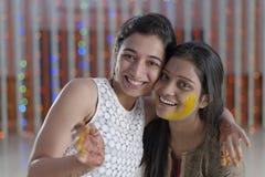 Indische Hindoese Bruid met kurkumadeeg op gezicht met zuster. Stock Foto's