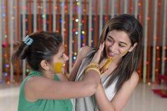 Indische Hindoese Bruid met kurkumadeeg op gezicht met zuster. stock foto
