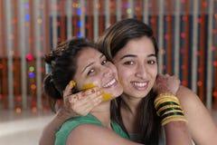 Indische Hindoese Bruid met kurkumadeeg op gezicht met zuster. royalty-vrije stock afbeelding