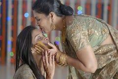 Indische Hindoese Bruid met kurkumadeeg op gezicht & moeder kussende bruid. Royalty-vrije Stock Afbeelding