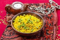 Indische Küche: Schüssel gelber Reis mit grünen Erbsen lizenzfreies stockbild