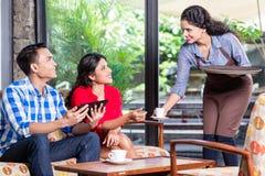 Indische Kellnerin, die Bestellungen im Café oder im Restaurant entgegennimmt stockbild