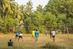 Indische Kerle, die draußen Volleyball auf einem grünen Dschungelfeld spielen stockfoto