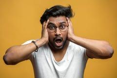 Indische knappe kerel die schok en wanhoop, wat betreft zijn hoofd met handen uitdrukken royalty-vrije stock foto