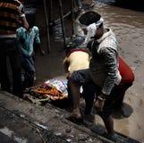 Indische Männer baden gestorbenen Verwandten im Ganges Stockfotos