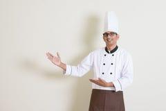 Indische mannelijke chef-kok in eenvormig tonend iets Royalty-vrije Stock Foto's
