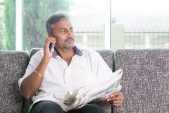 Indische Mannlesezeitung und nennen Telefon Lizenzfreie Stockfotos