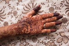 Indische mehndi (henna die schilderen) in woman'shand bij bloemrijke achtergrond stock foto