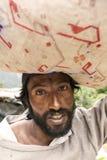Indische mens die grote zak op zijn hoofd dragen Stock Foto's