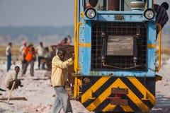 Indische mens die kleine trein met zout laden stock foto's