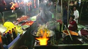 Indische mens die lokaal voedsel voorbereiden bij een straattribune in nacht in Mumbai stock footage