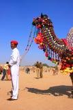 Indische mens die zich met zijn verfraaide kameel bij Woestijnfestival bevinden, Stock Foto