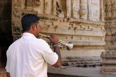 Indische mens met een bugel in tempel van Hampi, India Stock Afbeelding