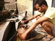 Indische mensen die waater uit een bron nemen Stock Afbeeldingen