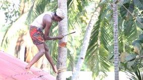 Indische mensentribunes op huisdak en karbonades onderaan palm stock footage
