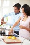 Indische Paare, die zu Hause Mahlzeit kochen Lizenzfreie Stockfotografie