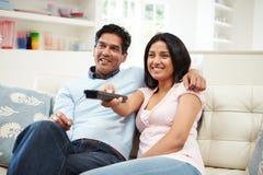 Indische Paare, die zusammen im Sofa Watching Fernsehen sitzen Lizenzfreie Stockfotos