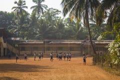 Indische schoolkinderenjongens en meisjes die voetbal blootvoets in de schoolyard spelen onder groene palm stock foto