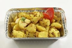 Indische schotel gebraden aardappel met komijn in het dienblad van de metaalfolie stock afbeeldingen