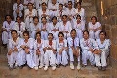 Indische Schulmädchen, die bei Qutub Minar, Delhi, Indien sitzen stockfotografie