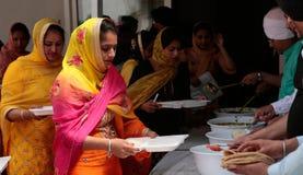 Indische Sikhfrauen nehmen ihr Mittagessen innerhalb ihres Tempels während Baisakhi-Feier in Mallorca lizenzfreie stockbilder