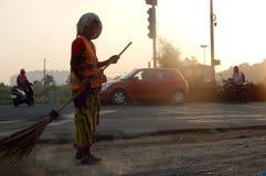 Indische städtische Arbeitskraftschleife die Straße auf eine traditionelle Art mit Besenstiel Lizenzfreie Stockbilder