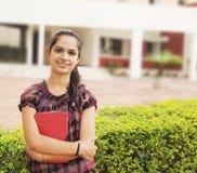 Indische Student die met boeken glimlacht Royalty-vrije Stock Foto's