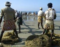 Indische vissers die in hun visnetten trekken Stock Fotografie