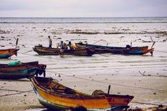 Indische vissers op het strand met hun boten stock afbeeldingen