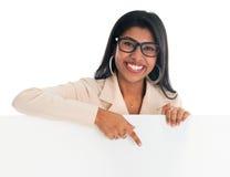 Indische vrouw die en aan leeg aanplakbord houden richten. Royalty-vrije Stock Foto's