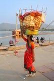 Indische vrouw die met mand op haar hoofd door de Mens Sagar Lake lopen royalty-vrije stock fotografie
