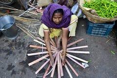 Indische vrouw die rieten mand op de straatmarkt maken Stock Foto
