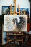 Indische vrouw in het schilderen van atelier op tribune met harp en het schilderen Royalty-vrije Stock Afbeelding