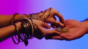 Indische vrouw met in hand oorringen voorraad De vrouw geeft een man haar juwelen, een gift als teken van vriendschap stock video