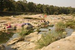 Indische Vrouwen die en Kleren wassen drogen door Wildernis stock afbeeldingen