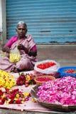 Indische vrouwen die kleurrijke bloemslinger verkopen op de plaats van de straatmarkt voor godsdienstceremonie Stock Foto's