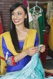 Indische weibliche Damenschneiderin, die beim Halten des Saris weg schaut stockbild