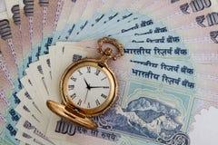 Indische Währungs-Rupien-Anmerkungen mit antiker Uhr Stockfoto