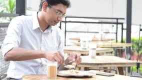 Indische zakenman die roti eten stock footage