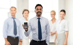 Indische zakenman met smartphone op kantoor royalty-vrije stock afbeelding