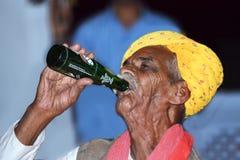 Indischer alter Mann, der kaltes Getränk trinkt Stockfotos