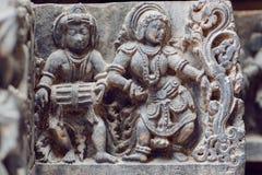 Indischer Architekturhintergrund, mit Schlagzeugermusiker und Tanzenfrau innerhalb des des 12. Jahrhundertstempels in Halebidu, I Stockfoto