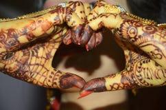 Indischer Bräutigam, der ihre Hand als schöner Nahaufnahmeschuß der Herzform formt stockfoto