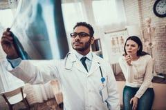Indischer Doktor, der Patienten im Büro sieht Doktor betrachtet den Röntgenstrahl der Frau stockbilder