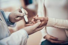 Indischer Doktor, der Patienten im Büro sieht Doktor misst Blutzucker der schwangeren Frau mit Tochter lizenzfreie stockfotografie